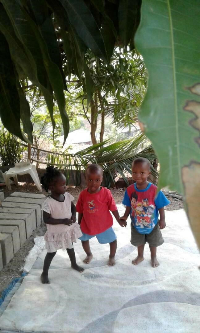 Three children playing in Sierra Leone. Charlie in the middle, between Aminata (in white) and Justice (in blue), 2018.