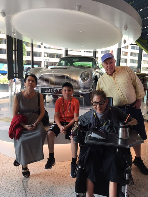 Sheri with her sister, brother-in-law, and great-nephew at the new Spy Museum, modeling in front of the famous James Bond Aston Martin, 8-19.