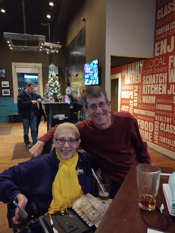Sheri and Rockefeller College Board co-chair Frank sharing drinks in an Albany bar, watching Albany get slammed by Montana in a football playoff game,12-19.