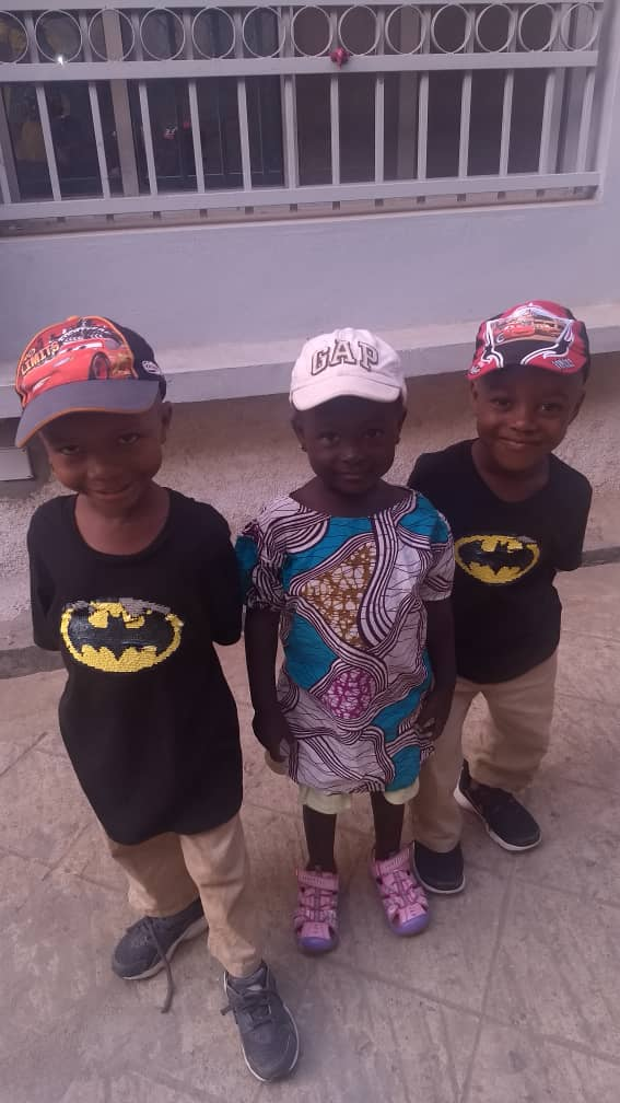 "Charlie (far right) with his buddies Aminata (middle) and Justice (far left); the boys love Batman courtesy of ""Daddy Tony,"" 3-19."