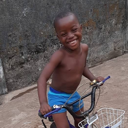 "Our ""adopted"" son Charlie happily riding his new bike in Sierra Leone, 1-20."