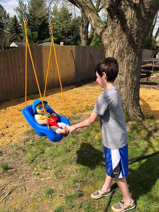 Happy on Wheels' great-nephew, Santino, pushing his  baby brother  in a swing, 5-20.