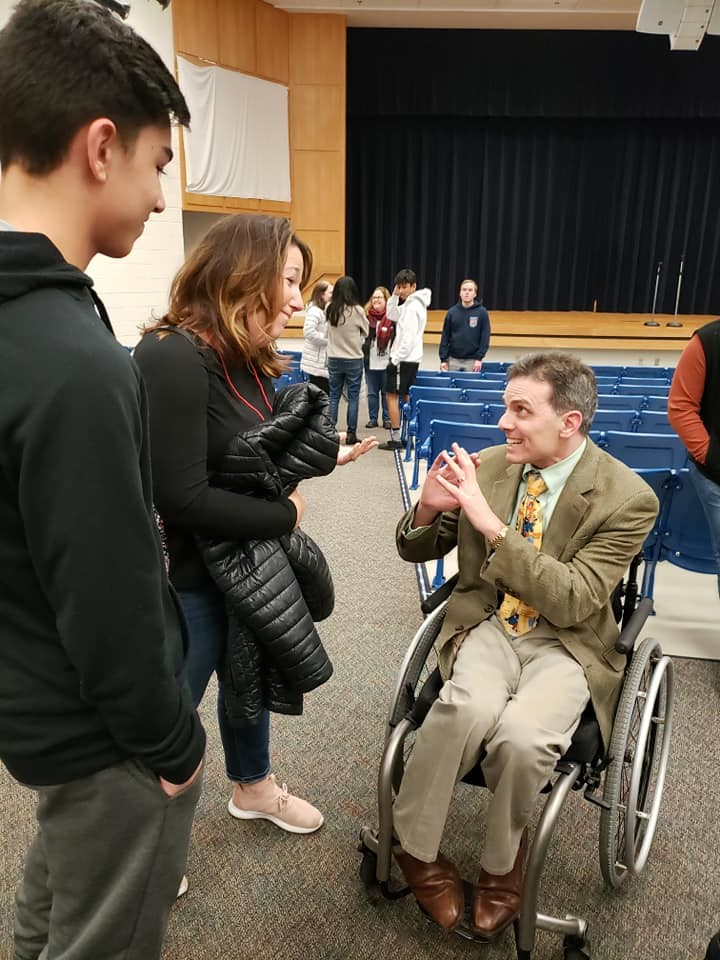 Tony chatting with a participant and his Mom following a Happy on Wheels presentation to the Young Men's Service League, 1-20.
