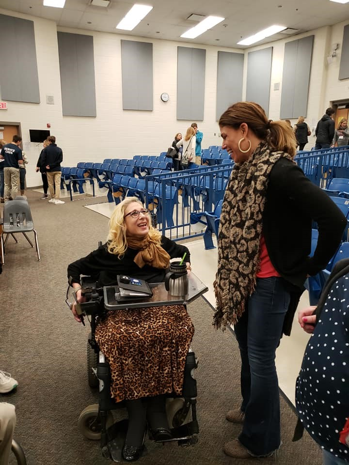 Sheri chatting with an audience member following a Happy on Wheels presentation to the Young Men's Service League, 1-20.