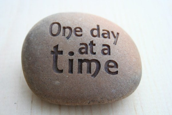 "Stone with ""One day at a time"" carved in it."