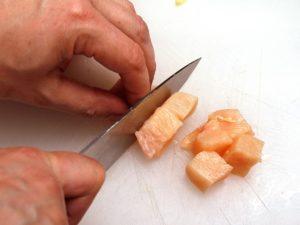 Someone cutting chicken meat