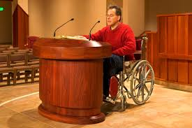 Wheelchair user at a lectern on an altar.