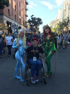 A wheelchair user with two cosplayers
