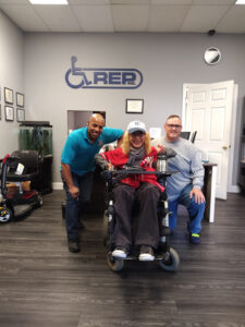 A very happy wheelchair user with two techs from REP