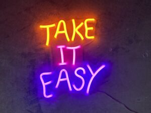 "Graphic of a neon sign that says ""Take It Easy."""