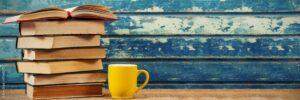 A stack of books next to a coffee mug.