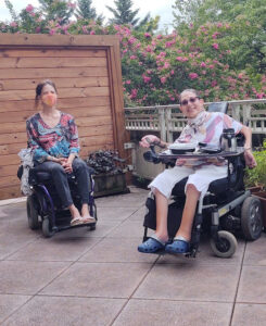 Two people sitting in powerchairs.